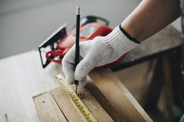 hand on a wood and meter - 3 Things to Do Before Renovating Your Home