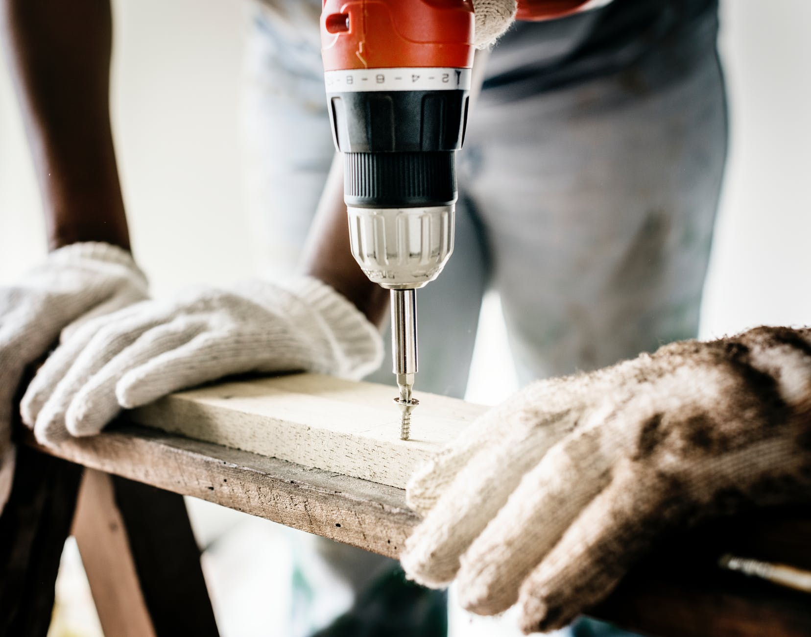 repairman doing screw drilling - 2 Things to Consider When Hiring a Kitchen Contractor